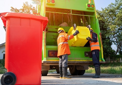 Two garbage men working together on emptying dustbins for trash removal with truck loading waste and trash bin