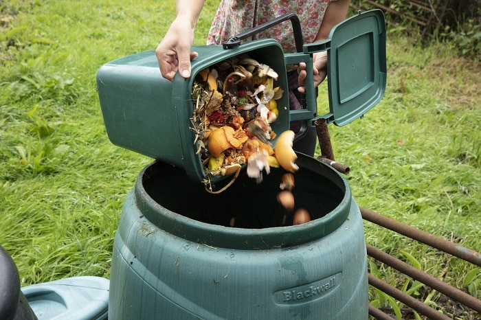 woman emptying a green home composting bin into an outdoor compost bin to reduce waste
