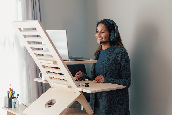 Young woman working on laptop at standing desk with earphones